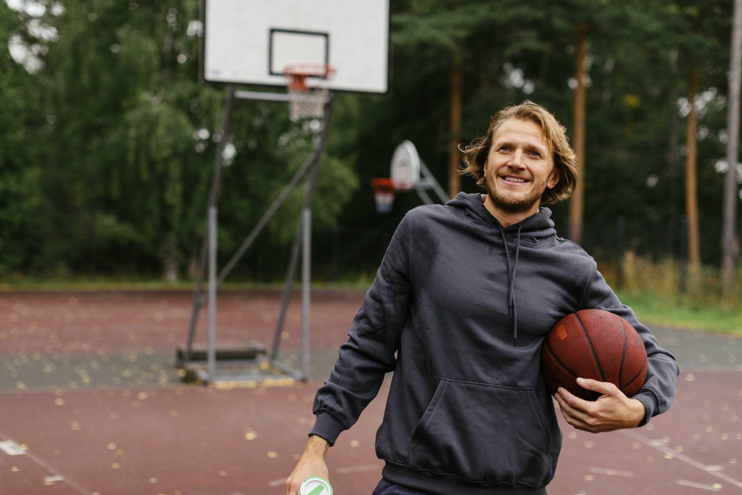 mies koripallokentällä, pallo kainaliossaan