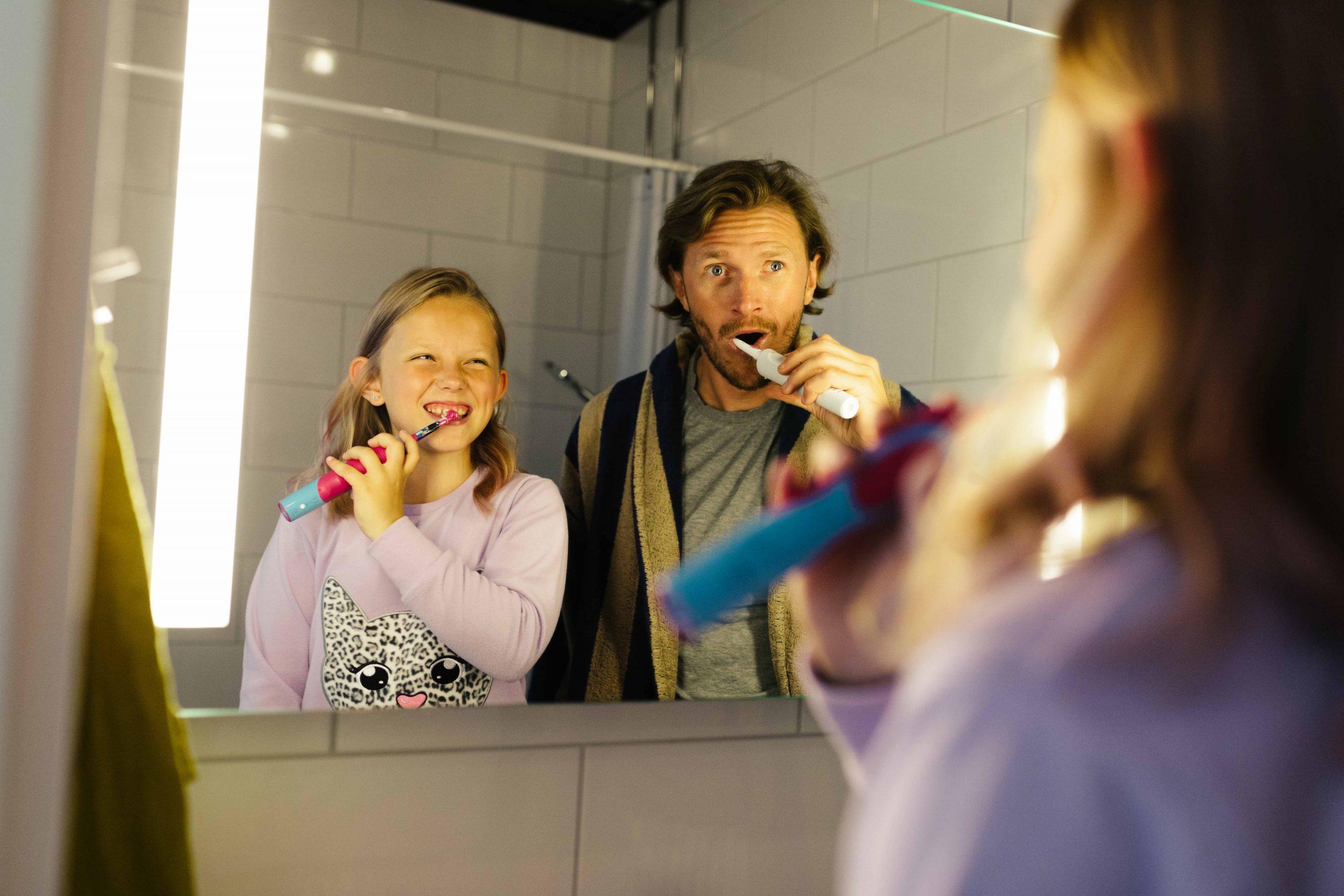 Lapsi ja mies pesemässä hsampaita peilin edessä