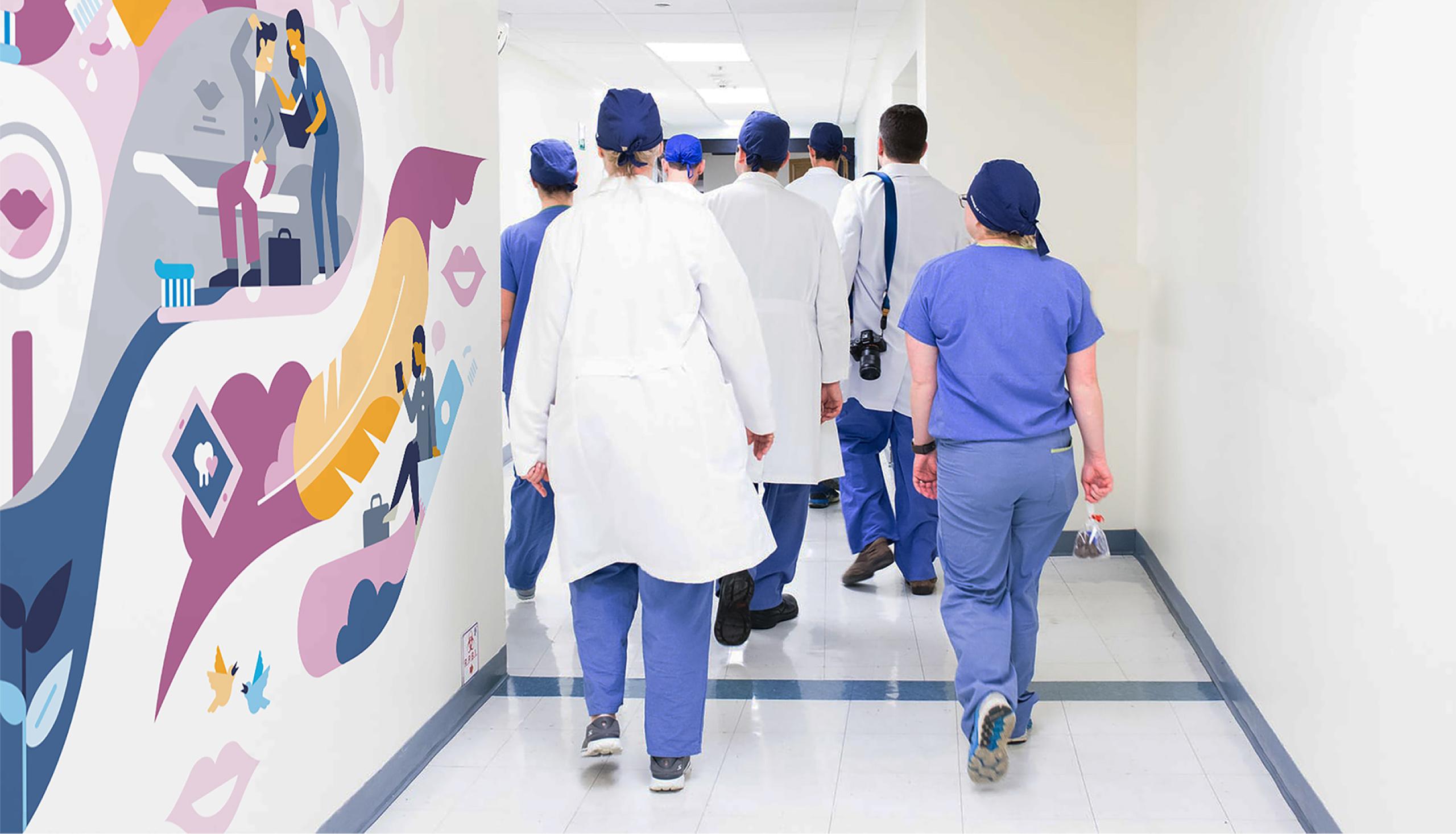 Terveydenhuollon henkilökuntaa kävelemässä käytävällä, seinässä on kuvituksista teetetty seinämaalaus.